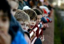 <p>School children peer over a wall for a glimpse of a Northern Bottle-nosed Whale in the river Thames near Battersea Bridge in south London January 20, 2006. REUTERS/Dylan Martinez</p>