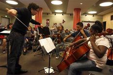 """<p>El conductor venezolano Gustavo Dudamel enseña música a niños de la Orquestra Juvenil de LA, en Los Angeles 6 dic 2008. Con Dudamel, la filarmónica de Los Angeles no sólo obtiene a un reconocido director, sino que también recibe la experiencia de alguien formado en """"El Sistema"""", la elogiada cadena venezolana de escuelas de música que ha ayudado a miles de niños a alejarse de la violencia y las drogas en los barrios más desprotegidos. REUTERS/Lucy Nicholson</p>"""