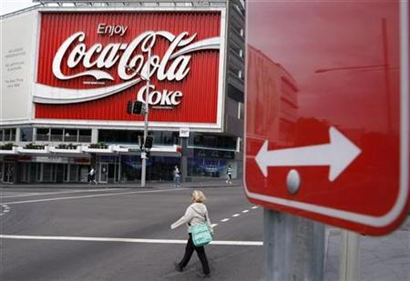 A pedestrian crosses a road in front of an outdoor Coca-Cola advertisement in Sydney November 17, 2008. REUTERS/Tim Wimborne