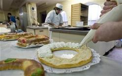 "<p>A pastry chief fills Christmas cakes known as ""rosco de reyes"" with whipped cream in a pastry factory in Burgos, northern Spain January 5, 2008. REUTERS/Felix Ordonez</p>"