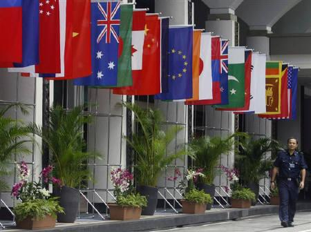 File photo of a police officer walking past the national flags of countries attending the Association of Southeast Asian Nations (ASEAN) Ministerial Meeting and ASEAN Regional Forum in Singapore. REUTERS/Vivek Prakash/Files