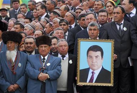A member of the Halk Maslakhaty or People's Council holds a portrait of the late Turkmen leader Saparmurat Niyazov as delegates gather for a session of the council near the ancient city of Mary in southeastern Turkmenistan March 30, 2007. REUTERS/Michael Steen