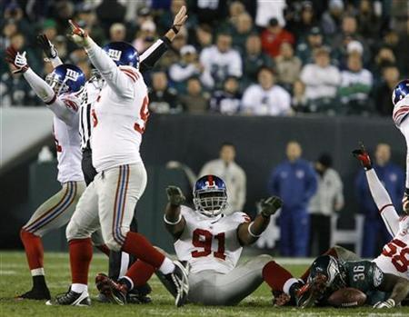 New York Giants defensive end Justin Tuck (91) celebrates after stopping Philadelphia Eagles running back Brian Westbrook (36) for no gain on a fourth down during the fourth quarter of NFL football game action in Philadelphia, Pennsylvania, in this file photo from November 9, 2008. REUTERS/Tim Shaffer