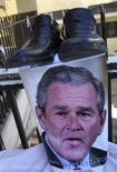 <p>Um pôster com uma foto do presidente norte-americano, George W. Bush, é visto embaixo de um par de sapastos durante um protesto em uma universidade em Beirut, no dia 17 de dezembro. A sapatada que o presidente dos Estados Unidos, George W. Bush, quase levou no rosto no Iraque, no domingo, inspirou a criação de um jogo online em que o internauta tenta acertar com sapatos a imagem do líder norte-americano. REUTERS/ Mohamed Azakir (LEBANON)</p>