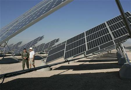 Col. Dave Belote (L), commander of Nellis Air Force Base, and Eric Vander Leest, a photovoltaic system technician for SunPower Corp., walk through an array of solar photovoltaic panels at the base in Las Vegas, Nevada in this picture taken August 1, 2008. REUTERS/Steve Marcus