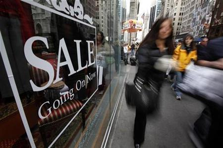Shoppers walk down Fifth Avenue past a sale sign in the window of a Brooks Brothers store in New York, December 7, 2008. REUTERS/Chip East