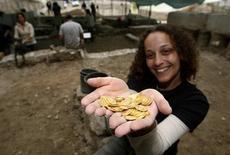 <p>Una voluntaria británica sostiene monedas de oro que ayudó en desenterrar durante excavaciones en Jerusalén, 22 dic 2008. Excavadores desenterraron un tesoro de monedas de oro de más de 1.300 años de antigüedad debajo de un estacionamiento de autos al lado de las paredes viejas de Jerusalén, dijo el lunes la Autoridad Israelí de Antigüedades. REUTERS/Ronen Zvulun</p>