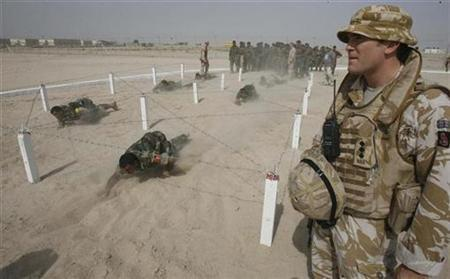A British soldier stands near Iraqi trainees crawling under barbed wires during military training conducted by British forces for Iraqi soldiers at a joint military base in Basra, 420 km (260 miles) southeast of Baghdad, in this October 20, 2008 file photo. Political squabbling in Iraq's parliament threatened again on Tuesday to hold up a measure needed by December 31 to permit troops from Britain, Australia and a handful of other countries to remain in Iraq next year. REUTERS/Atef Hassan