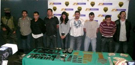 Miss Sinaloa, Laura Zuniga (C), and seven men are presented to media in Guadalajara, Mexico, December 23, 2008. The 23-year-old Mexican beauty queen and international pageant winner was arrested with a group of suspected drug traffickers, assault rifles, bullets and cash, police said on Tuesday. REUTERS/Secretaria Seguridad Publica de Jalisco