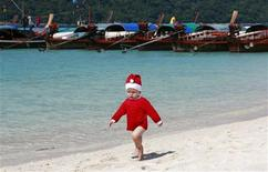 <p>A boy wearing a Santa hat runs on a beach past taxi boats in Turatao Marine National Park off the Andaman Sea in southern Thailand's Satun province on December 22, 2008. From empty sun loungers at luxury hotels to vacant bar stools in dingy fleshpots, tourism in Thailand is going through its worst slump in decades, a result of the global economic slowdown and its own political turmoil. Picture taken December 22, 2008. REUTERS/Arthur Jones Dionio</p>
