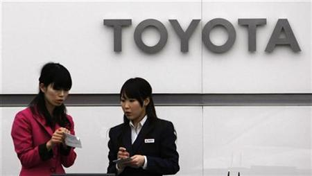Receptionist of Toyota Motor Corp are seen beneath of its company logo at its Tokyo office December 24, 2008. REUTERS/Kim Kyung-Hoon