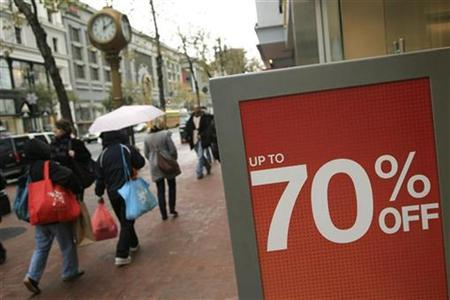 Last minute holiday shoppers walk past a sign at a retail establishment that has slashed prices by as much as 70 percent, in San Francisco, California December 24, 2008. REUTERS/Robert Galbraith