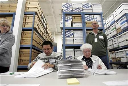 Election judges Willy Lee (L) and Joanne Caspersen recount marked ballots cast for the 2008 Minnesota senate race between former Saturday Night Live comedian Al Franken (DFL-MN) and incumbent Norm Coleman (R-MN) at an elections warehouse in Minneapolis November 19, 2008. REUTERS/Eric Miller