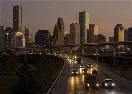Traffic flows at dusk with the downtown Houston skyline in the background as night falls on America's fastest growing large city in this file photo from October 3, 2008. REUTERS/Richard Carson