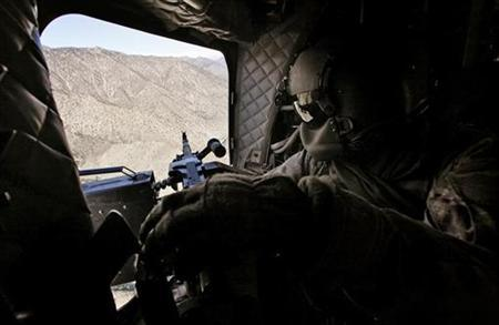 A door gunner on a U.S. Army Chinook helicopter keeps a watch on the terrain during a resupply mission in eastern Afghanistan December 25, 2008. REUTERS/Bob Strong
