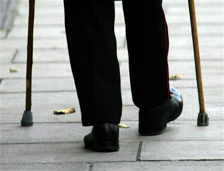 An elderly person walks with the aid of walking sticks in London, November 29, 2005. REUTERS/Toby Melville