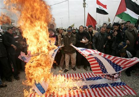 Demonstrators burn mock U.S. flags and Israeli flag during a protest in Baghdad's Sadr City January 9, 2009 against Israel's attacks in Gaza. REUTERS/Sattar al-Rubaie