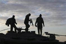 <p>Израильские солдаты на танке близ сектора Газа 11 января 2009 года. Израильские лидеры приняли решение направить резервистов в сектор Газа, где уже более двух недель идет военная операция против ХАМАС. REUTERS/Baz Ratner</p>