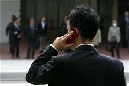 A man uses his mobile phone while waiting to cross a road outside Tokyo Station in Japan November 17, 2008. REUTERS/Stringer