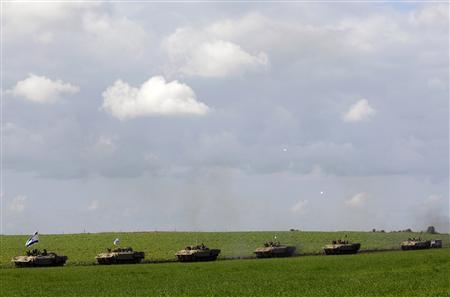 A convoy of Israeli armoured personnel carriers (APC) moves after crossing into Israel from the Gaza Strip January 18, 2009. Hamas said on Sunday it would cease fire immediately along with other militant groups in the Gaza Strip and give Israel, which already declared a unilateral truce, a week to pull its troops out of the territory. REUTERS/Amir Cohen