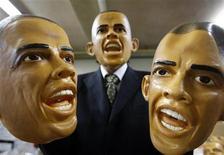 """<p>Сотрудник японской фабрики Ogawa Rubber Inc держит в руках резиновые маски, изображающие избранного президента США Барака Обаму, 19 января 2009 года """"Обамомания"""" уверенно шагает по планете благодаря популярности первого в истории темнокожего президента США Барака Обамы. REUTERS/Yuriko Nakao (JAPAN)</p>"""