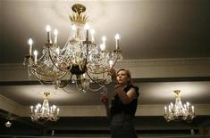 <p>A worker for Bonhams auctioneers poses under a chandelier at London's Cafe Royal December 22, 2008. REUTERS/Andrew Winning</p>