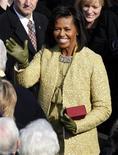 <p>Michelle Obama saluda al llegar a la ceremonia inaugural de su esposo, Barack Obama, como presidente de Estados Unidos en Washington, 20 ene 2009. Michelle Obama, a quien muchos consideran como un nuevo ícono de estilo estadounidense, asumió el martes su lugar en la escena mundial vistiendo un traje de color amarillo, algo poco tradicional que remeció al mundo de la moda. REUTERS/Jim Young</p>