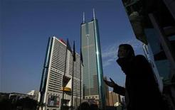<p>A man talks on the mobile phone outside the Shenzhen Stocks Exchange opposite to the 384-metre (1,260 ft) tall skyscraper at Shun Hing Square in the southern Chinese city of Shenzhen in Guangdong province November 25, 2008. REUTERS/Bobby Yip</p>