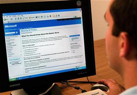 A Microsoft Windows user downloads a patch from Microsoft's website to protect his computer from a virus in New York, August 14, 2003. REUTERS/Jeff Christensen