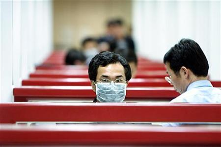 A Taiwan immigration officer wears protective mask at Taipei's Chiang Kai-shek International Airport on March 18, 2003. REUTERS/Simon Kwong