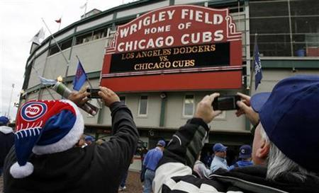 Chicago Cubs fans take photos of the marquee outside of Wrigley Field before the start of Game 1 of the MLB National League Divisional Series playoff baseball game between the Los Angeles Dodgers and the Chicago Cubs in Chicago, October 1, 2008. REUTERS/John Gress