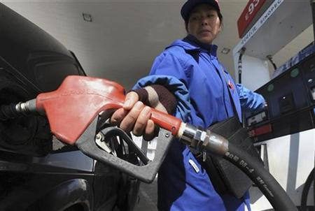An employee fills a vehicle at a gas station in Hefei, Anhui province, China January 1, 2009. REUTERS/Jianan Yu