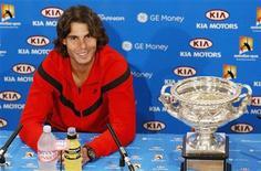 <p>Il tennista spagnolo Rafael Nadal sorridente accanto al trofeo degli Open d'Australia. REUTERS/Mick Tsikas</p>