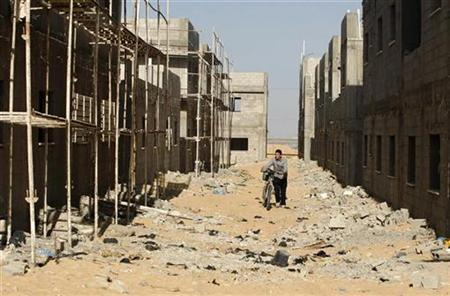 A Palestinian walks past an unfinished building at a construction site in Khan Younis in the southern Gaza Strip January 29, 2009. REUTERS/Ibraheem Abu Mustafa