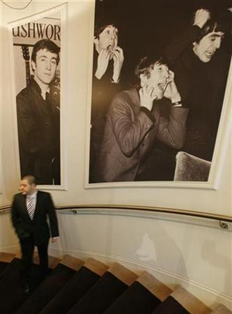A member of staff passes pictures of the Beatles on the main staircase at the Hard Days Night Hotel in Liverpool, northern England February 1, 2008. REUTERS/Phil Noble