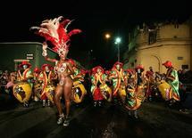 """<p>Miembros de una """"comparsa"""", un grupo de carnaval, participan durante el desfile de """"llamadas"""" en Montevideo, 5 feb 2009. La comunidad negra de Uruguay, por mucho tiempo opacada en el foco cultural y político del país, está disfrutando de un despertar mientras sus raíces africanas son festejadas en un vibrante carnaval de tambores. REUTERS/Andres Stapff (URUGUAY)</p>"""