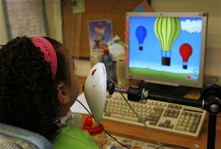 Maria Amin, who turns six on Thursday, plays a computer game from her wheelchair in a rehabilitation hospital in Jerusalem August 29, 2007. REUTERS/Yannis Behrakis