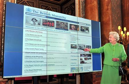 Britain's Queen Elizabeth II looks at the new layout of the British Monarchy website on a giant screen after she relaunched the site at Buckingham Palace central London, February 12, 2009. REUTERS/John Stillwell/Pool