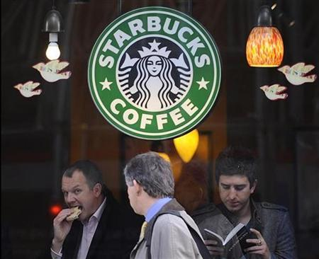 A pedestrian passes a branch of Starbucks Coffee, in central London November 25, 2008. REUTERS/Toby Melville