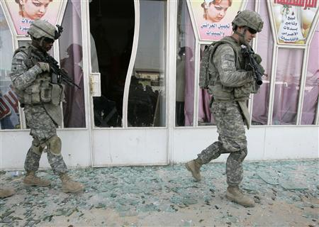 U.S. soldiers walk on shattered glass at the site a bomb attack in Baghdad's Sadr City February 15, 2009. REUTERS/Mohammed Ameen