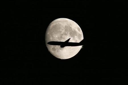 An aircraft is silhouetted against the moon as it flies over London September 12, 2008. REUTERS/John Voos