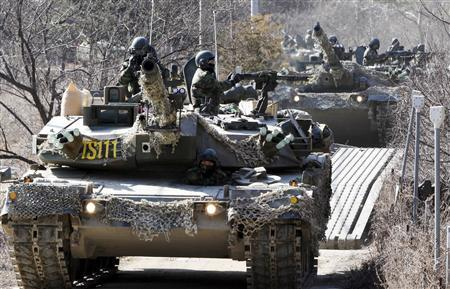 South Korean Army tanks move on a temporary bridge to cross a river during a winter season military exercise against a possible attack from North Korea in Pocheon, about 46 km (28 miles) northeast of Seoul, February 17, 2009. REUTERS/Kim Do-Yun/Yonhap