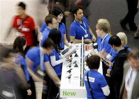Nokia's staff are seen at their stand at the GSMA Mobile World Congress in Barcelona, February 19, 2009. REUTERS/Gustau Nacarino