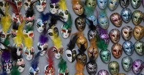 <p>Distintas máscaras cuelgan en la plaza San Marcos durante el Carnval de Venecia, Italia, 14 feb 2009. - Desde cajas de leche a globos aerostáticos y desde la reina Isabel I a diseños inspirados en cubos de basura, el Carnaval de Venecia vio de todo en lo que se refiere a disfraces. REUTERS/Alessandro Bianchi</p>
