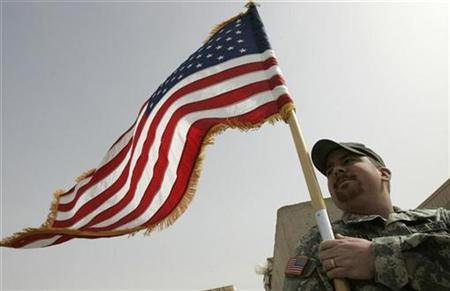 A U.S. soldier holds the Stars and Stripes flag during a ceremony marking the fielding of the 10,000th mine resistant armor protected vehicles at Camp Liberty in Baghdad February 20, 2009. REUTERS/Mohammed Ameen