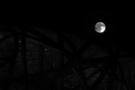 The moon is seen above the National Stadium, also know and the Bird's Nest, in Beijing August 16, 2008. REUTERS/Kevin Coombs