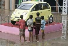 <p>Alcuni bambini guardano un modello in esposizione della Nano, di Tata Motors. REUTERS/Parth Sanyal (INDIA)</p>