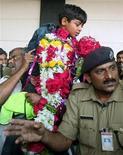 """<p>Una multitud celebra la llegada del pequeño actor Azharuddin Ismail del filme 'Slumdog Millionaire' en el aeropuerto internacional de Mumbai, 26 feb 2009. Caramelos, guirnaldas y cientos de fotógrafos recibieron el jueves a los niños actores de """"Slumdog Millionaire"""" en su retorno a India, después de que el país celebrara el triunfo de la película en los premios Oscar. REUTERS/Punit Paranjpe (INDIA)</p>"""