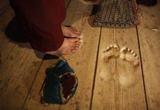 <p>The feet of monk Hua Chi are seen close to the footprints made by him by praying at the same spot for decades, at a monastery near Tongren, Qinghai province February 25, 2009. REUTERS/Reinhard Krause</p>