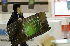 <p>Un uomo trasporta un cartello pubblicitario a forma di cellulare a una fiera. REUTERS/Hannibal Hanschke</p>